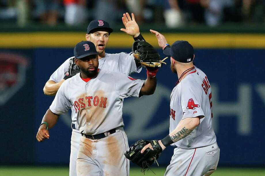 Grady Sizemore (back), Jackie Bradley Jr. and Jonny Gomes (right) celebrate Boston's victory in Atlanta. Photo: Kevin C. Cox / Getty Images / 2014 Getty Images