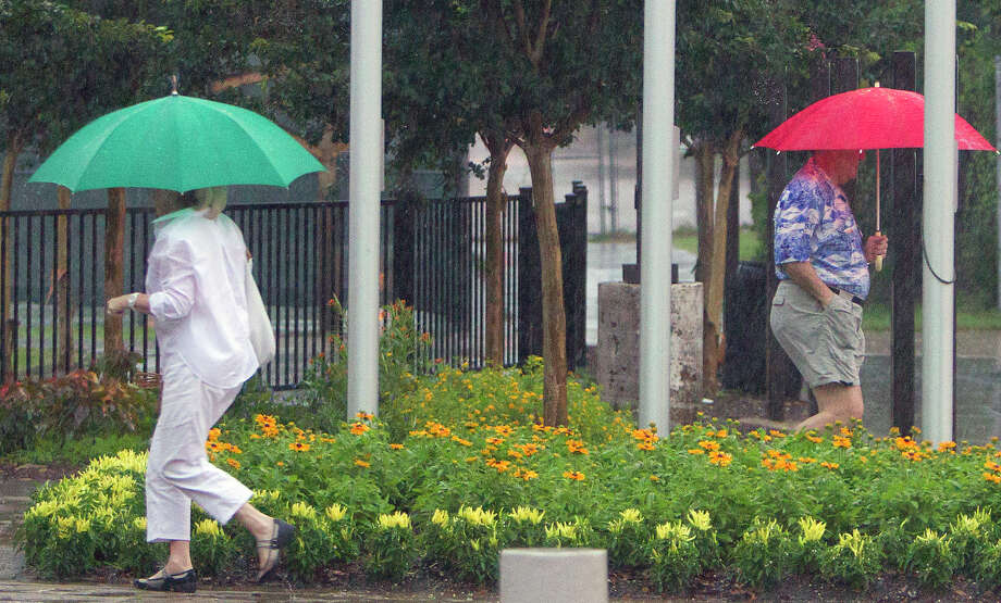 On another rainy day, umbrellas were in vogue Tuesday as voters came and went to cast their votes at the Metropolitan Multi-Services Center, Photo: Cody Duty, Staff / © 2014 Houston Chronicle