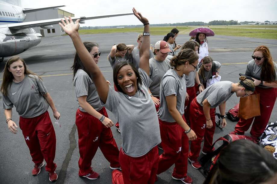 Alabama outfielder Andrea Hawkins cheers as the softball team gathers its bags before boarding a flight to Oklahoma City for the NCAA Women's College World Series, Tuesday, May 27, 2014, in Tuscaloosa, Ala. (AP Photo/AL.com, Vasha Hunt) MAGS OUT Photo: Vasha Hunt, Associated Press