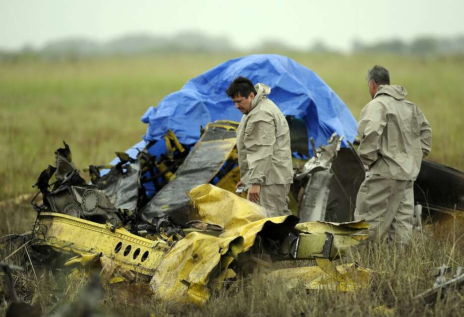 Officials look over the scene where a crop duster plane crashed near Gueydan, La., Tuesday, May 27, 2014. Vermilion Parish sheriff's deputies say the pilot of the plance died in the crash. (AP Photo/The Daily Advertiser, Paul Kieu) NO SALES Photo: Paul Kieu, Associated Press