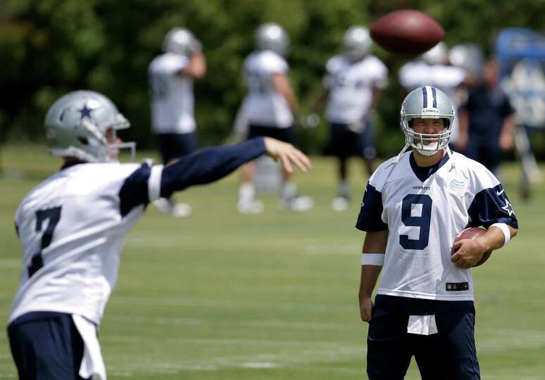 Dallas Cowboys quarterback Tony Romo watches as Caleb Hanie throws a pass during an NFL football org