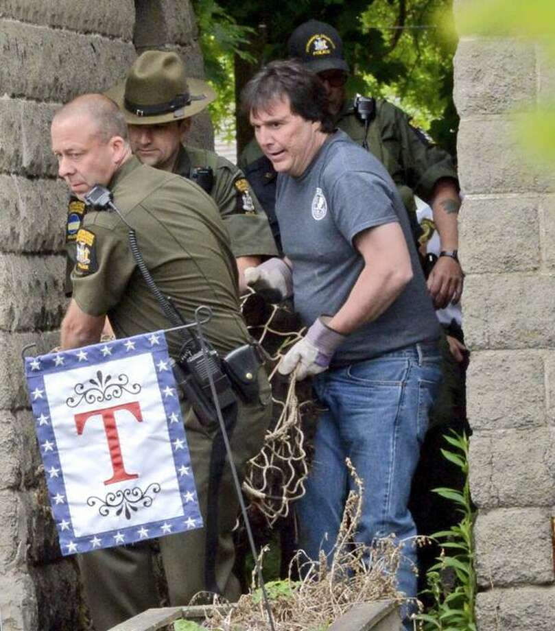The bear in Albany has been captured. Department of Environmental Conservation officers carry the bear from the scene after he fell from a pine tree behind a home on Rose Court. (Skip Dickstein / Times Union)