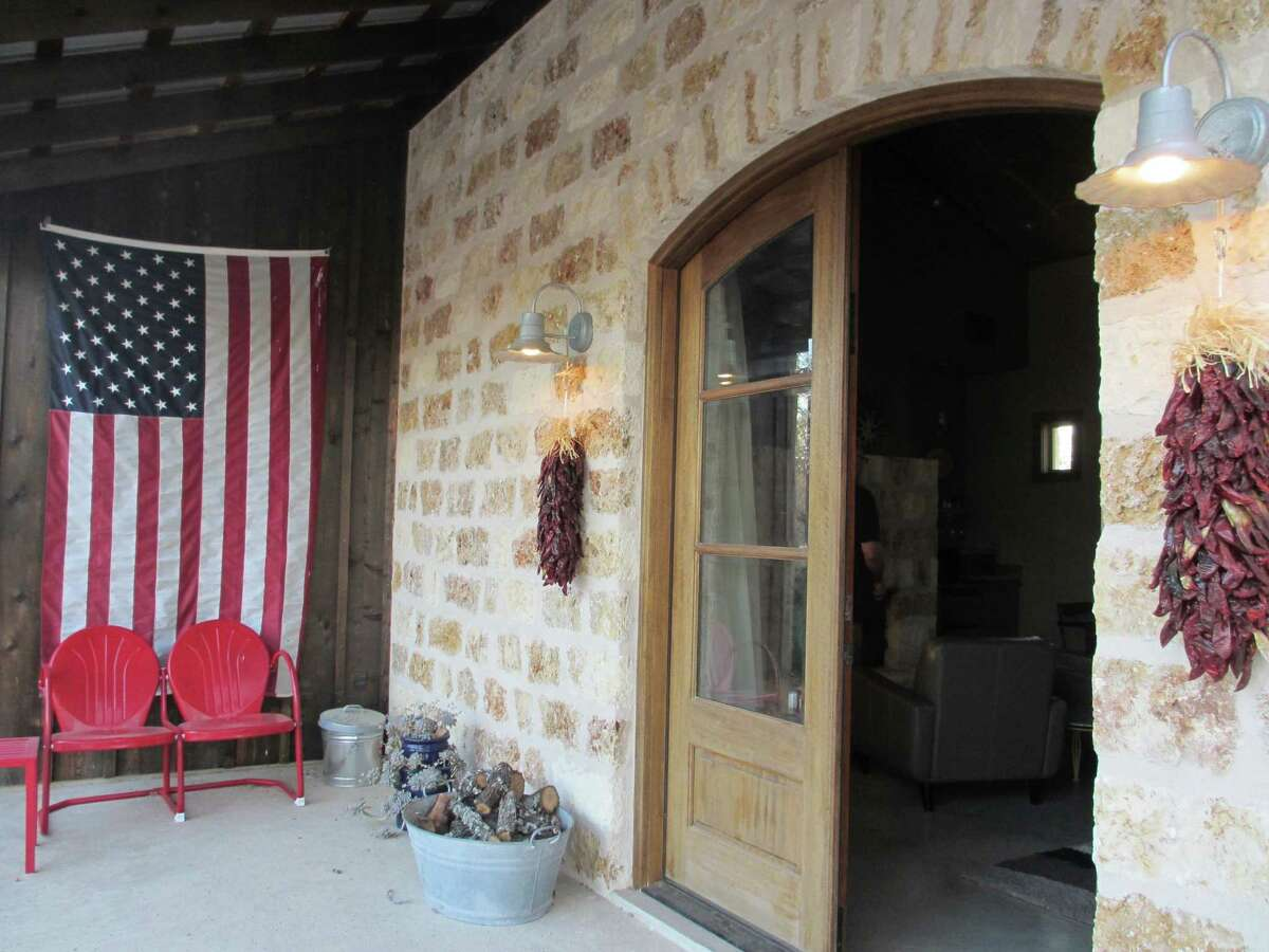 Picture perfect accommodations Stay at a cozy bed and breakfast or ranch like this. Red retro chairs perfect for the two of you sit in front of an American flag on the wide porch at the Coyote Cabin at Double Deer Ranch north of Fredericksburg.