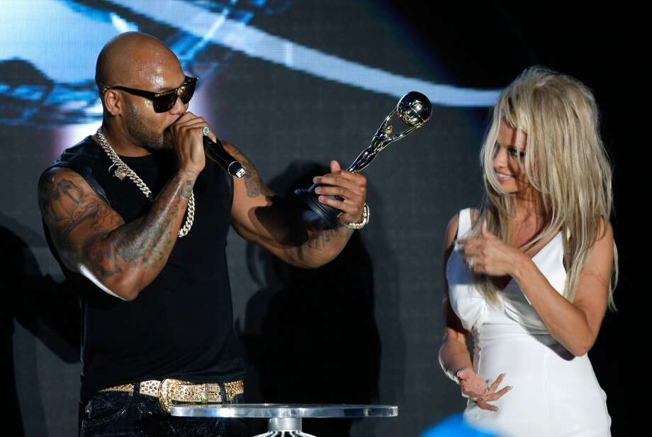 American rap singer Flo Rida accepts an award from American actress Pamela Anderson during the World Music Awards in Monaco, Tuesday, May 27 2014. Photo: Claude Paris, Associated Press