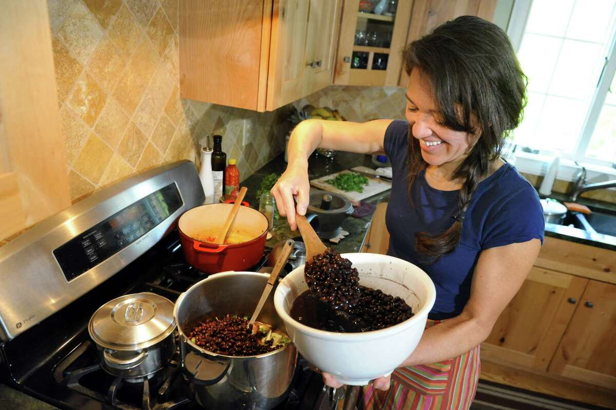 Ellie Markovitch, a native of Brazil, adds black beans to a national dish at her home on Wednesday, May 21, 2014, in Brunswick, N.Y. (Cindy Schultz / Times Union)