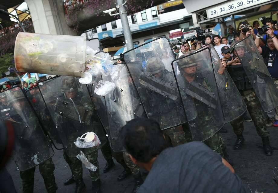 A protester, foreground, throws a garbage bin at a line of Thai soldiers during an anti-coup demonstration at the Victory Monument in Bangkok, Thailand Wednesday, May 28, 2014. Thailand's new military junta aired videos Wednesday on television stations nationwide showing some of the prominent political figures it has detained as part of an effort to convince the public that detainees in army custody are being treated well. (AP Photo/Wason Wanichakorn) Photo: Wason Wanichakorn, Associated Press