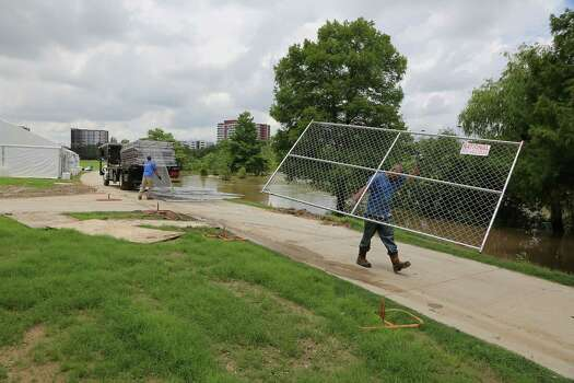 High water in Buffalo Bayou flows as MJ Jones left, and George Soto right, with National Construction Rentals install fences for the upcoming Free Press Summer Festival near Eleanor Tinsley Park along the banks of Buffalo Bayou Wednesday, May 28, 2014, in Houston. Photo: James Nielsen, Houston Chronicle / © 2014  Houston Chronicle