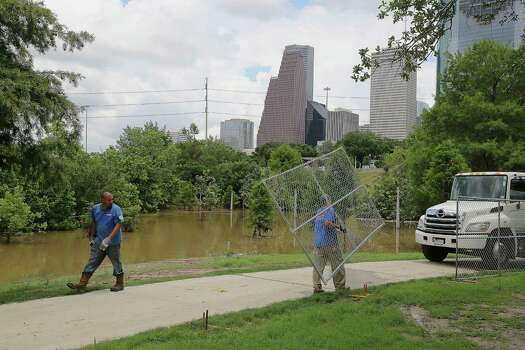 High water in Buffalo Bayou flows as George Soto left, and MJ Jones right, with National Construction Rentals install fences for the upcoming Free Press Summer Festival near Eleanor Tinsley Park along the banks of Buffalo Bayou Wednesday, May 28, 2014, in Houston. Photo: James Nielsen, Houston Chronicle / © 2014  Houston Chronicle
