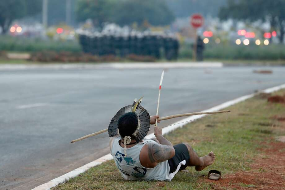 A David-vs.-Goliath moment in Brasilia:An indigenous protester in traditional headdress prepares to fire an arrow 