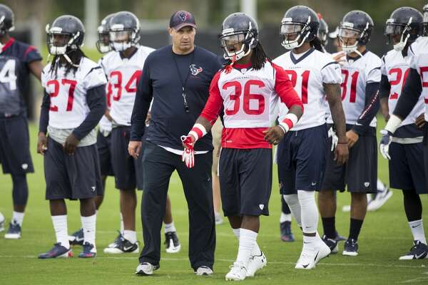 Texans head coach Bill O'Brien, center, talks to safety D.J. Swearinger (36) during warm up drills.
