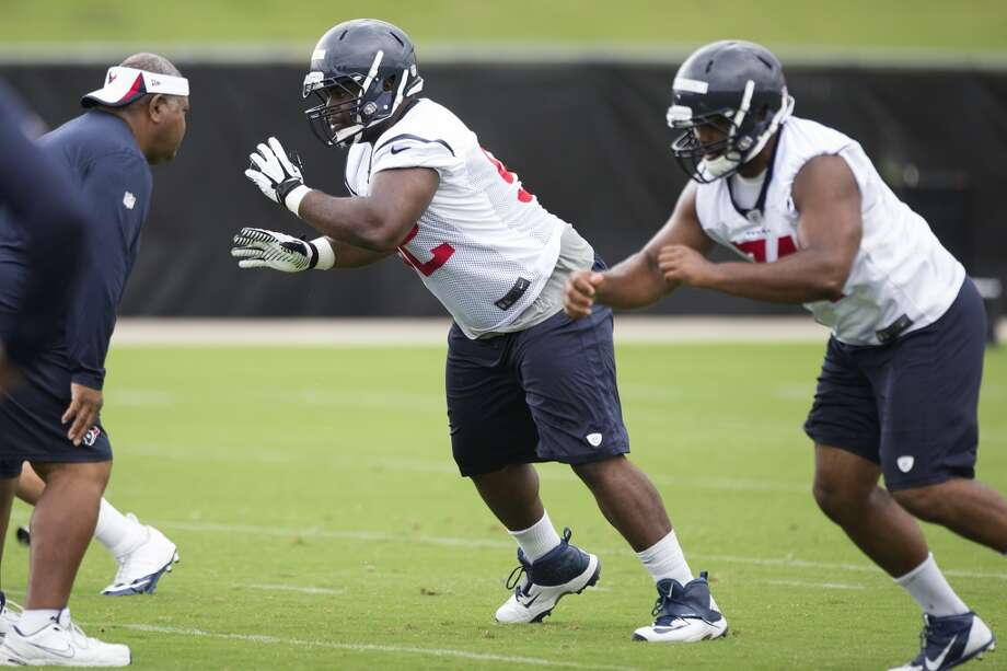 Texans defensive coordinator Romeo Crennell, left, runs defensive linemen Louis Nix III (92) and Julius Warmsley (74) through a drill. Photo: Brett Coomer, Houston Chronicle