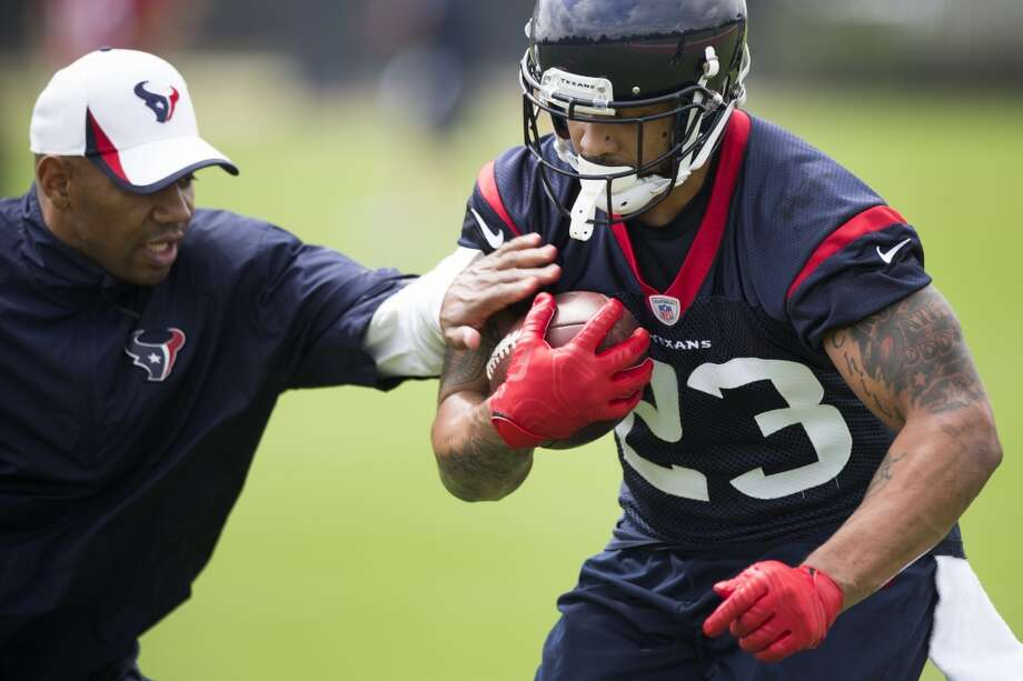 Texans running backs coach Charles London, left, reaches in to try and knock the ball away from running back Arian Foster (23). Photo: Brett Coomer, Houston Chronicle