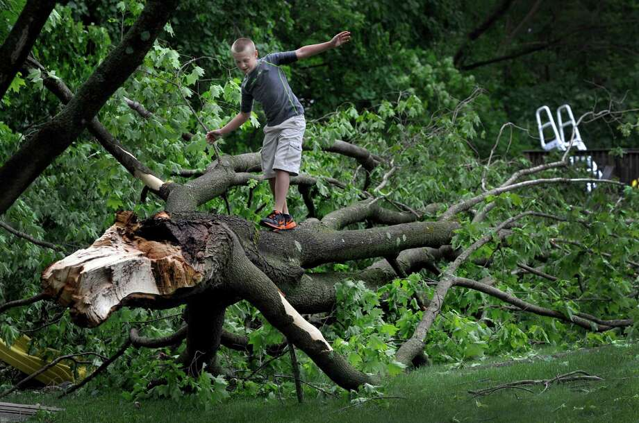 Logan Lucas, 10, plays on a huge branch that came down on his famlies yard on Russelingl Ridge Road in New Milford, Conn., during a rain storm Tuesday, night. Wednesday, may 28, 2014. Photo: Carol Kaliff / The News-Times