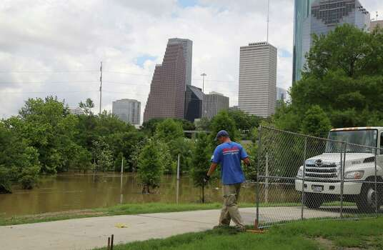High water in Buffalo Bayou flows as MJ Jones right, with National Construction Rentals installs fences for the upcoming Free Press Summer Festival near Eleanor Tinsley Park along the banks of Buffalo Bayou Wednesday, May 28, 2014, in Houston. Photo: James Nielsen, Houston Chronicle / © 2014  Houston Chronicle