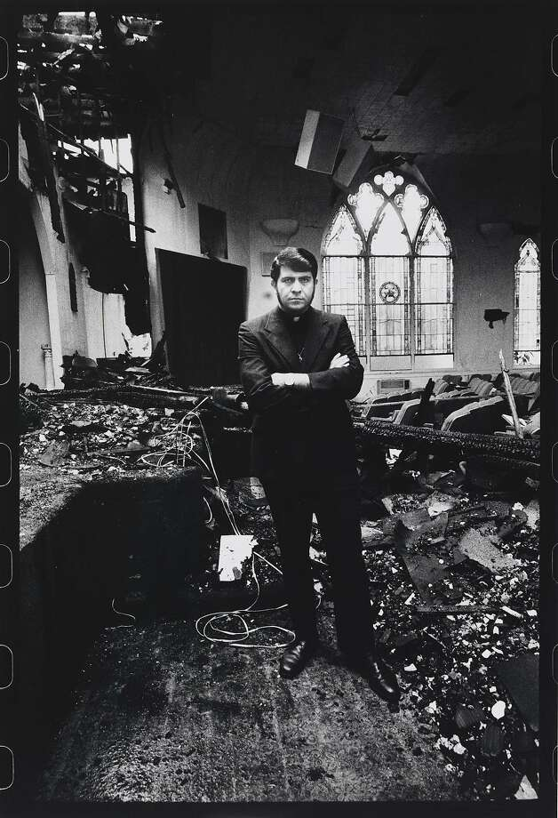 The Rev. Troy Perry, founder of the Metropolitan Community Church, stands amid ruins after a firebomb in this photograph featured in the de Young's Anthony Friedkin exhibition. Photo: Anthony Friedkin