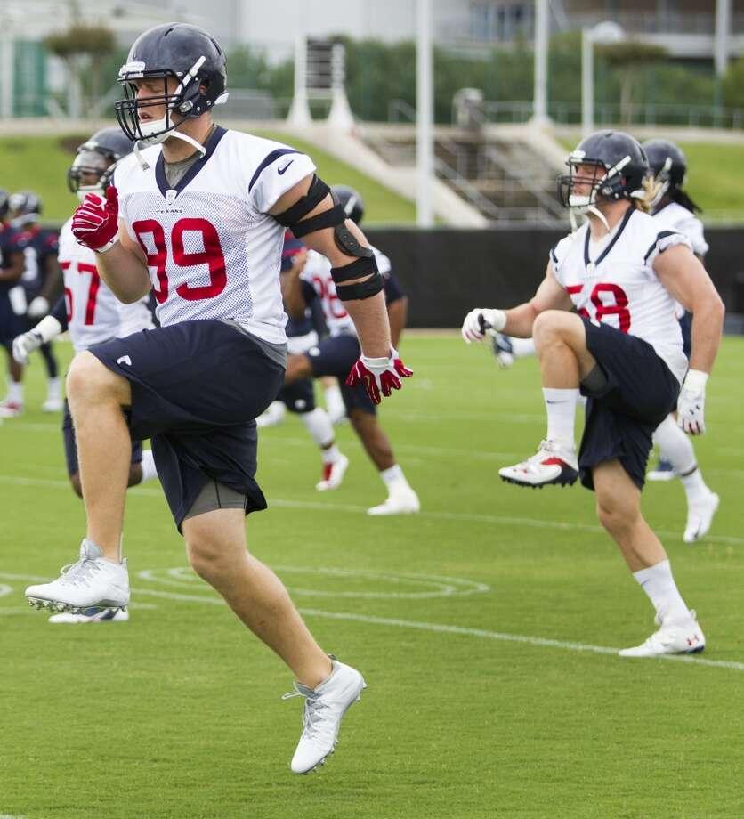 Texans defensive end J.J. Watt (99) and linebacker Brooks Reed (58) run warm up drills. Photo: Brett Coomer, Houston Chronicle