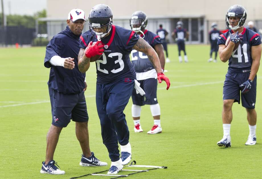 Texans running back Arian Foster (23) runs a drill with running backs coach Charles London, left, followed by Jonathan Grimes (41). Photo: Brett Coomer, Houston Chronicle