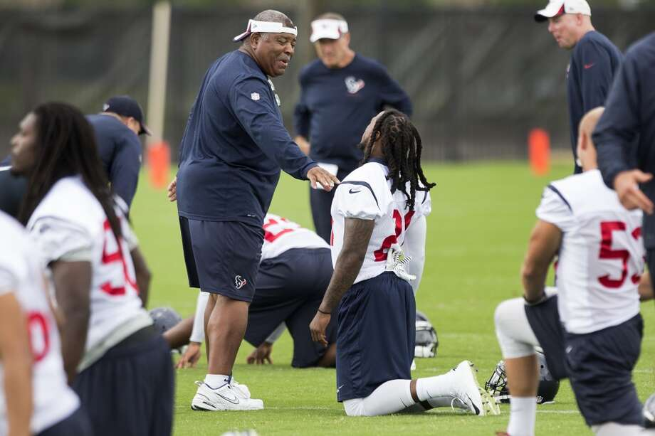 Texans defensive coordinator Romeo Crennell, left, talks to safety kendrick Lewis (21). Photo: Brett Coomer, Houston Chronicle