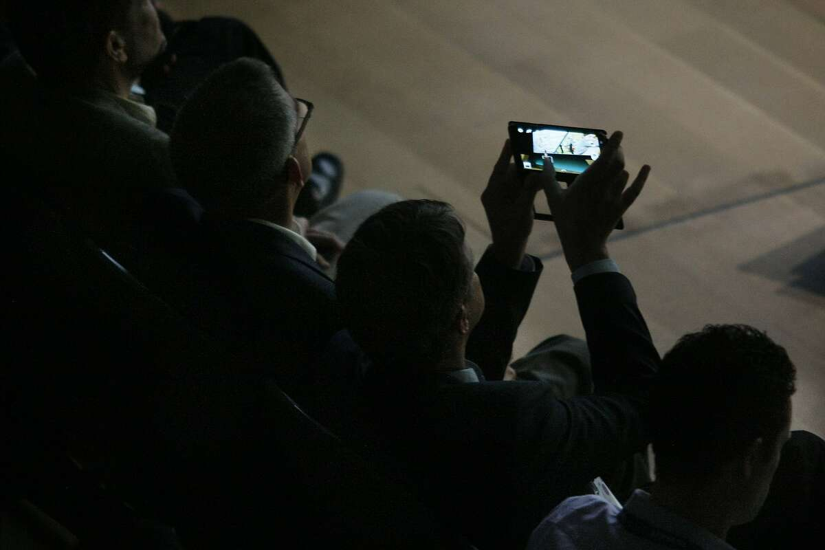 An attendee takes a photo of the unveiling of Samsung's new Simband at the SF JAZZ Center in San Francisco, Calif. on Wednesday, May 28, 2014. Samsung announced a wristband that would enable users to monitor their health more closely.