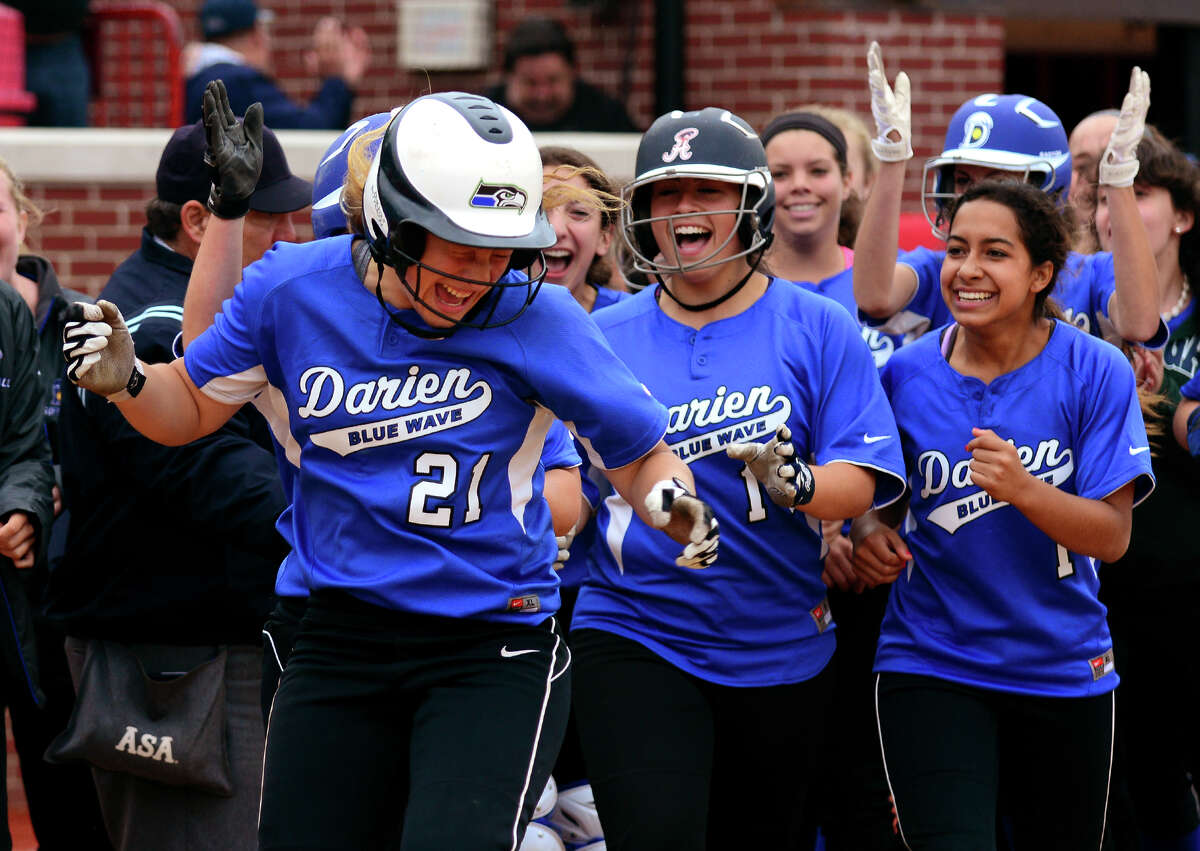 Teammates surround Darien's Erika Osherow at home plate after she hit a home run in the seventh inning to beat Westhill 4-1, during FCIAC Softball Championship semi-final action at Sacred Heart University in Fairfield, Conn. on Wednesday May 28, 2014.