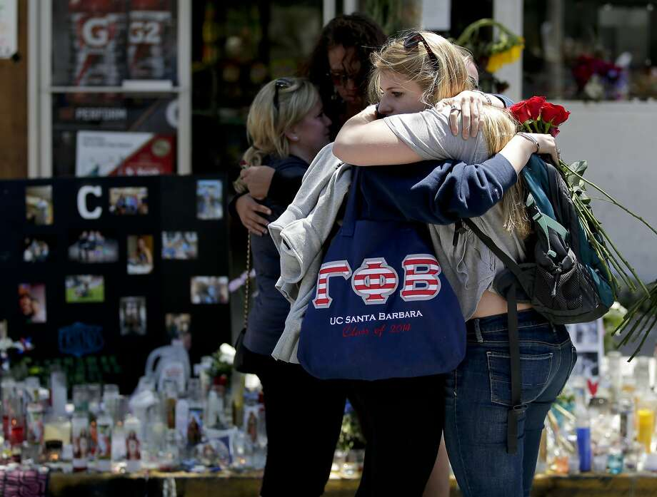 Mourners hug near IV Deli Mart in Isla Vista, where part of Friday's killing spree took place. Photo: Chris Carlson, Associated Press