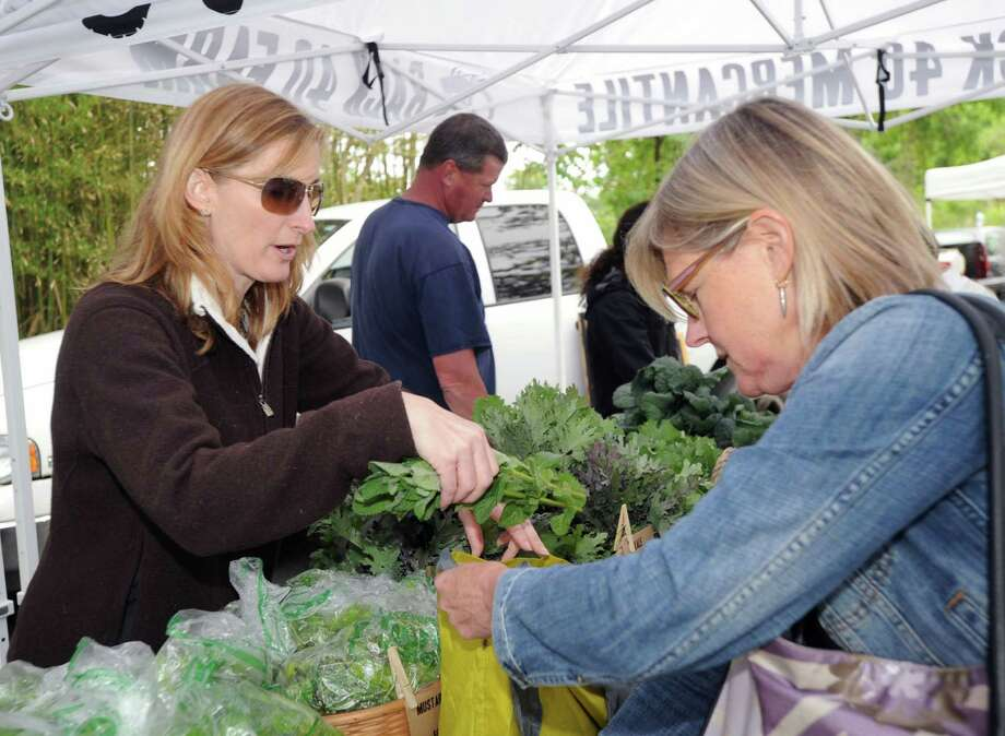 Old Greenwich resident, Lesley King, left, owner of Back 40 Group, that owns a farm in Washington Depot, Conn., sells kale to Rosanna Nissen, right, also of Old Greenwich, during the Old Greenwich Farmer's Market at the Presbyterian Church of Old Greenwich, Wednesday, May 28, 2014. Photo: Bob Luckey / Greenwich Time