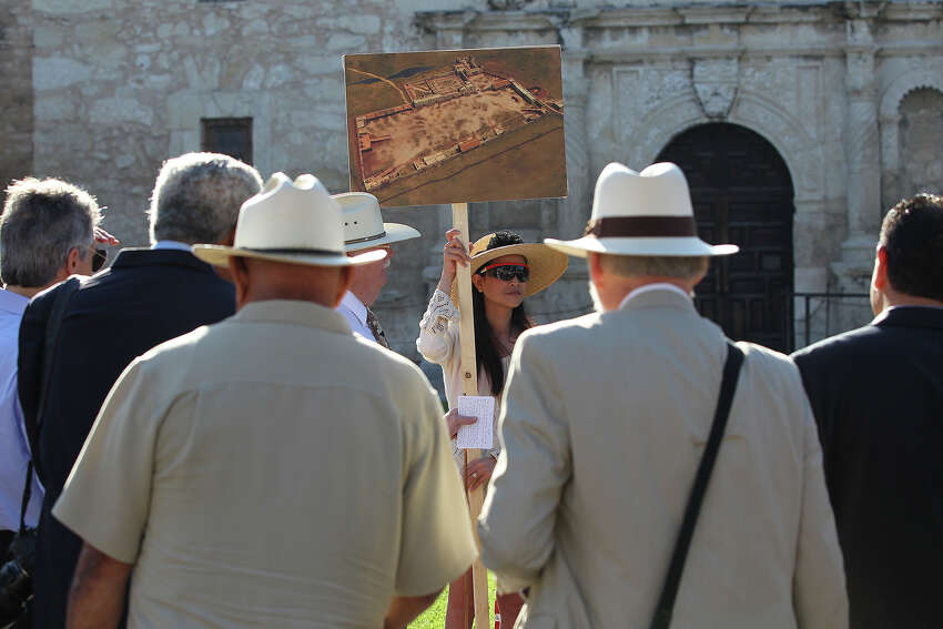 Sara Hinnant holds the drawing depicting the boundaries of the Alamo compound as the city's Alamo Plaza Commission tours the site on May 28, 2014.
