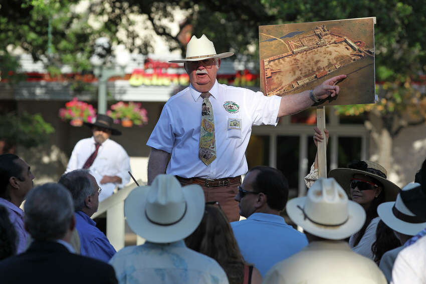 John L. Hinnant points out locations on a drawing of the original Alamo compound boundaries as the city's Alamo Plaza Commission tours the site on May 28, 2014.