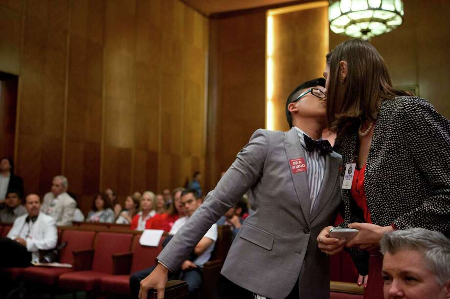 Melanie Pang, left, kisses her partner, Kendall Toarmina, after Pang voices her support for the equal rights ordinance. Photo: Marie D. De Jesus, Houston Chronicle / © 2014 Houston Chronicle