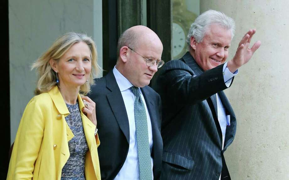 General Electric Co. CEO Jeffrey R. Immelt, right, and GE France chairwoman Clara Gaymard, left, leave the Elysee Palace following their meeting with French President Francois Hollande in Paris, Wednesday, May 28, 2014. General Electric Co. is seeking France's approval for its $17 billion bid to buy Alstom SA's energy division. Walking at center is GE Senior Vice President John L. Flannery Responsible for GE's mergers, acquisitions and divestiture activities worldwide.(AP Photo/Remy de la Mauviniere) ORG XMIT: DLM107 Photo: Remy De La Mauviniere / AP
