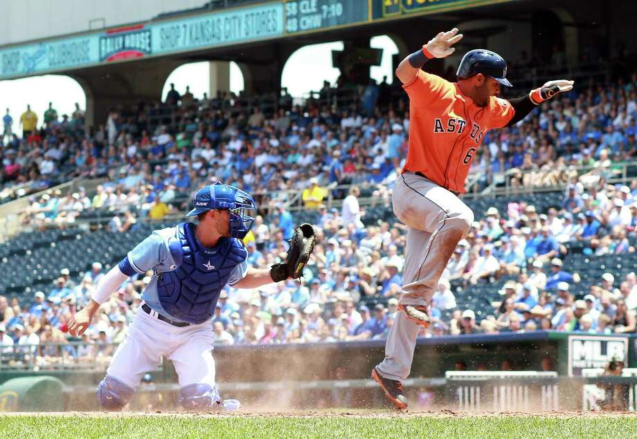 Jonathan Villar, right, plays keepaway in order to dodge Royals catcher Brett Hayes and score a second-inning run. Photo: Jamie Squire, Staff / 2014 Getty Images