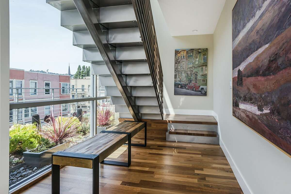 A steel and hardwood staircase leads to the upper level of the penthouse.