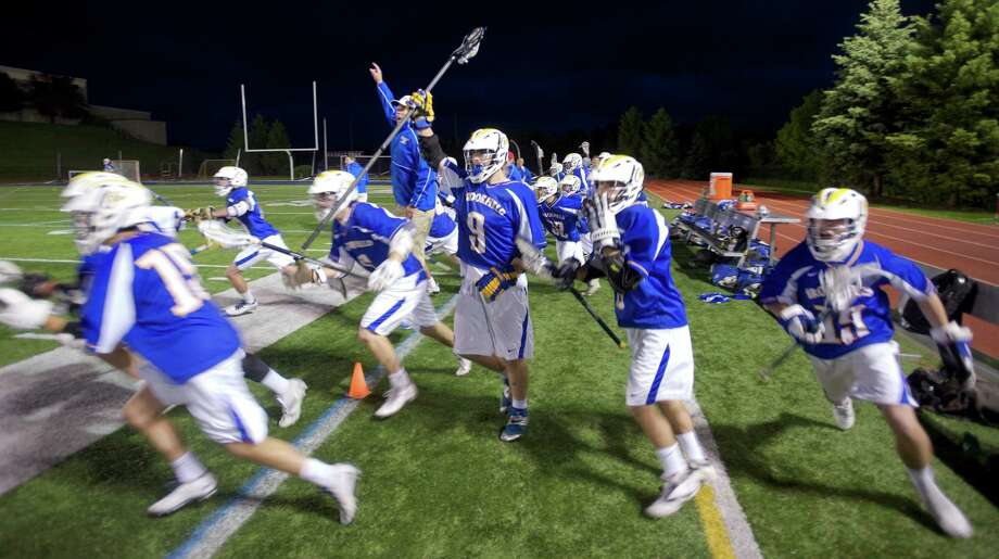 The Brookfield sideline celebrates after the winning goal was scored during overtime play in the SWC Division I boys lacrosse semifinals game between Joel Barlow of Redding and Brookfield High School, played at New Fairfield High School, New Fairfield, Conn, on Wednesday night, May 28, 2014. Brookfield won 10-9 in overtime. Photo: H John Voorhees III / The News-Times Freelance