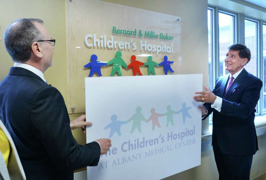 "William Duker of Westerlo, let, and Albany Med president and CEO James Barba unveil a new sign renaming The Children's Hospital ""The Bernard and Millie Duker Children's Hospital at Albany Medical Center"" during a news conference Wednesday May 28, 2014, in Albany, NY.  (John Carl D'Annibale / Times Union) Photo: John Carl D'Annibale / 00027069A"