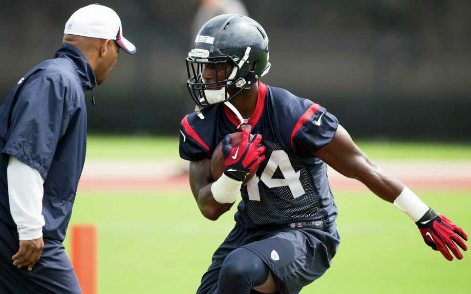 Sixth-round draft choice Alfred Blue, working on a drill with running backs coach Charles London during Wednesday's OTA, already has caught the eye of head coach Bill O'Brien. Photo: Brett Coomer, Staff / © 2014 Houston Chronicle