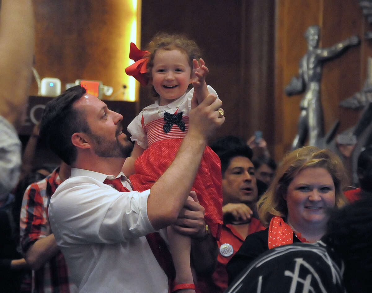 Ryan Leach holds Madeleine Schimmer, 4, as they and her mother, Sarah Schimmer, celebrate with a crowd at City Hall after the vote.