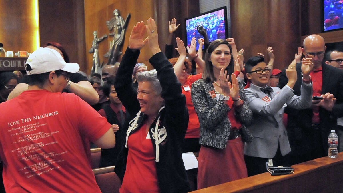 Debbie Kelly, second from left, joins in the celebration after approval of the equal rights ordinance.