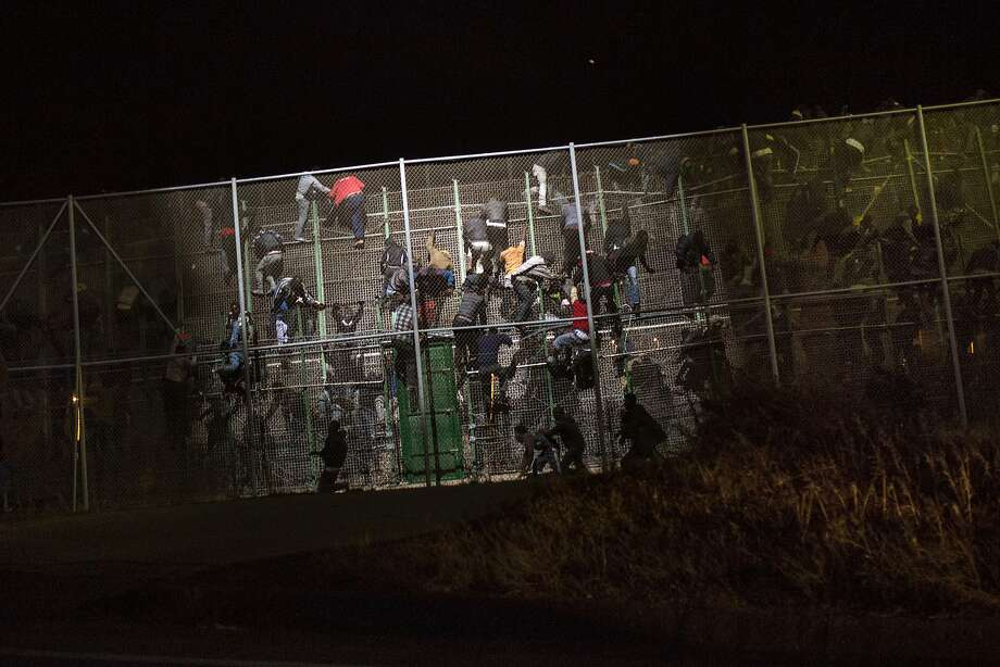 Sub-Saharan migrants, top, scale a metallic fence that divides Morocco and Melilla; a migrant, far left, sits atop a pole set in the fence as Spanish police stand guard, while a wounded man, near left, is helped by other migrants. Photo: Santi Palacios, Associated Press