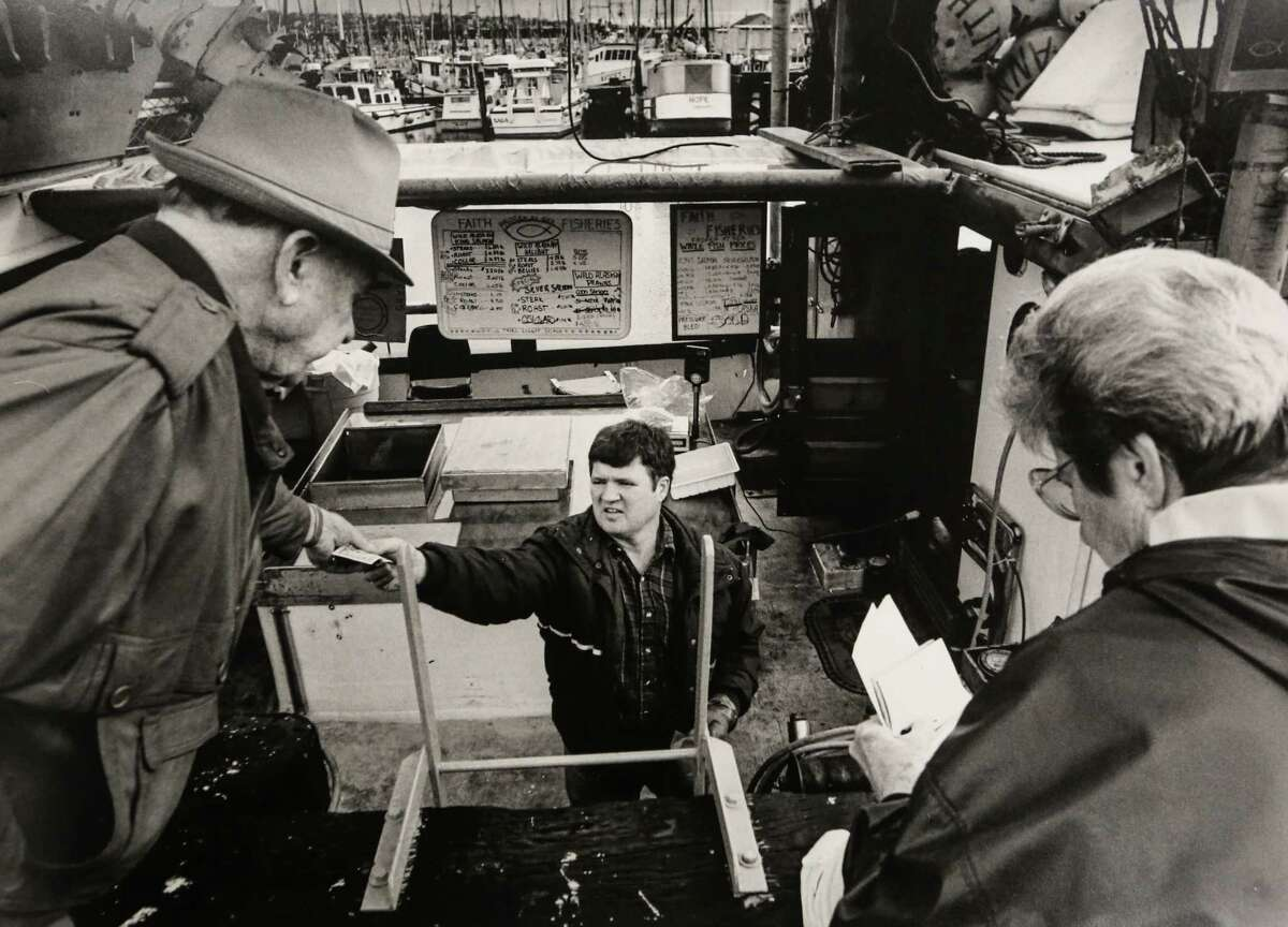 January 30, 1992 James Guilment passes change back to a customer while another customer writes a check for her order. Guilmet and his wife Marilyn sell fish from their boat, the Faith, from their tie-up at Fishermen's Terminal.