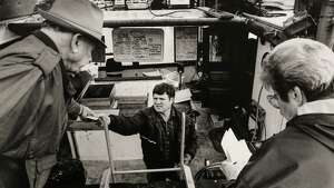 James Guilment passes change back to a customer while another customer writes a check for her order. Guilmet and his wife Marilyn sell fish from their boat, the Faith, from their tie-up at Fisherman's Terminal. January 30, 1992. Photo by Paul Joseph Brown