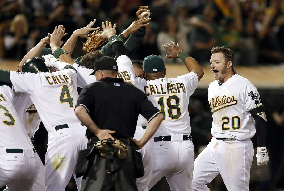 A's third baseman Josh Donaldson (20) is greeted at home after his three-run homer won the game in the ninth inning. Photo: Jeff Chiu, Associated Press