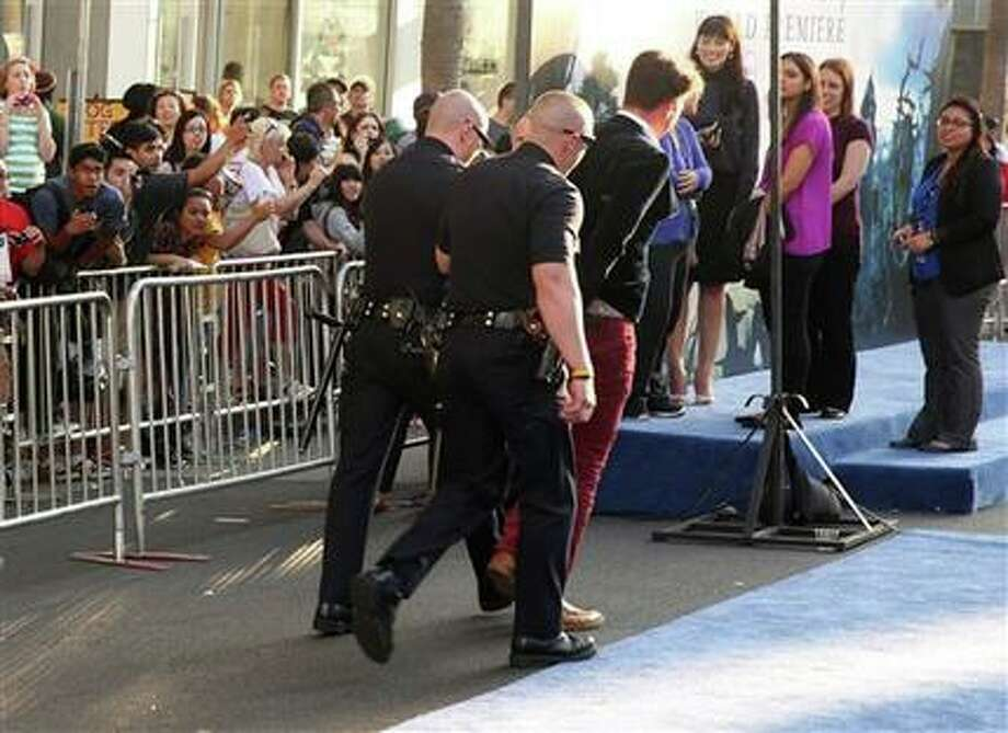 "A fan is walked off carpet in handcuffs after allegedly attacking Brad Pitt at the world premiere of ""Maleficent"" at the El Capitan Theatre on Wednesday, May 28, 2014, in Los Angeles. Photo: Matt Sayles, Associated Press / Invision"
