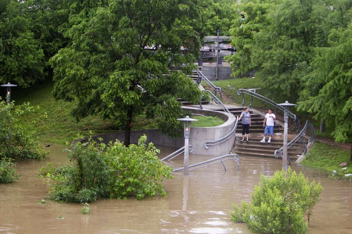 """Linda Flores, left, and her husband, Victor Flores, right, stand along the stairs adjacent to Buffalo Bayou, Wednesday, May 28, 2014, in Houston. The bayou swelled from the large amounts of rain Houston received. """"It's intense,"""" he said of the weather. (Cody Duty / Houston Chronicle)"""