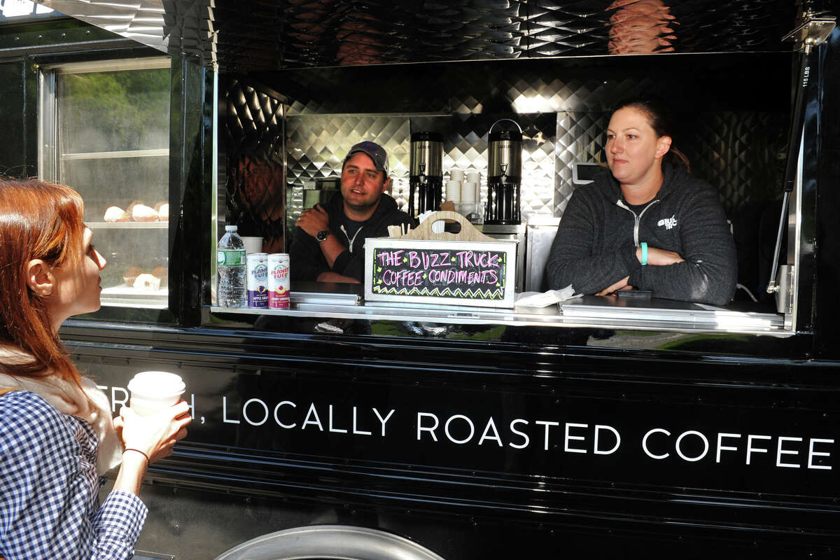 Alex and Jessica Grutkowski, owners of The Buzz Truck, talk with customer Barbara Lincoln at the Earthplace Nature Center, in Westport, Conn. May 29, 2014. The Buzz Truck is a converted school bus that sells coffee and other items.
