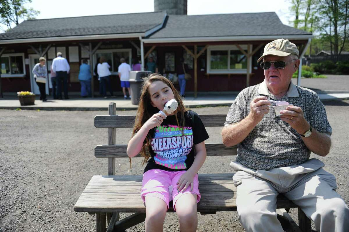 Sarah Brescia, 9, of New Milford, eats ice cream with her grandpa, Charlie Smith, of Bethel, at Ferris Acres Creamery in Newtown, Conn. Wednesday, May 14, 2014. The family farm has been around since 1964, passsed down from generation to generation, and is currently owned by Charles Ferris III along with his wife and kids.