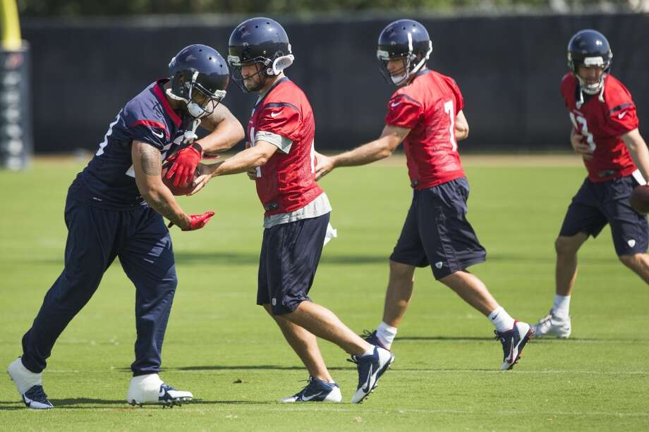 Texans quarterback Ryan Fitzpatrick (14) hands the ball off to running back Arian Foster, with quarterbacks Case Keenum (7) and T.J. Yates (13) in the background. Photo: Brett Coomer, Houston Chronicle