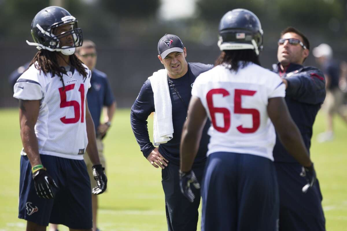 Texans head coach Bill O'Brien looks on as linebackers Paul Hazel (51) and Jason Ankrah (65) work with linebackers coach Mike Vrabel.