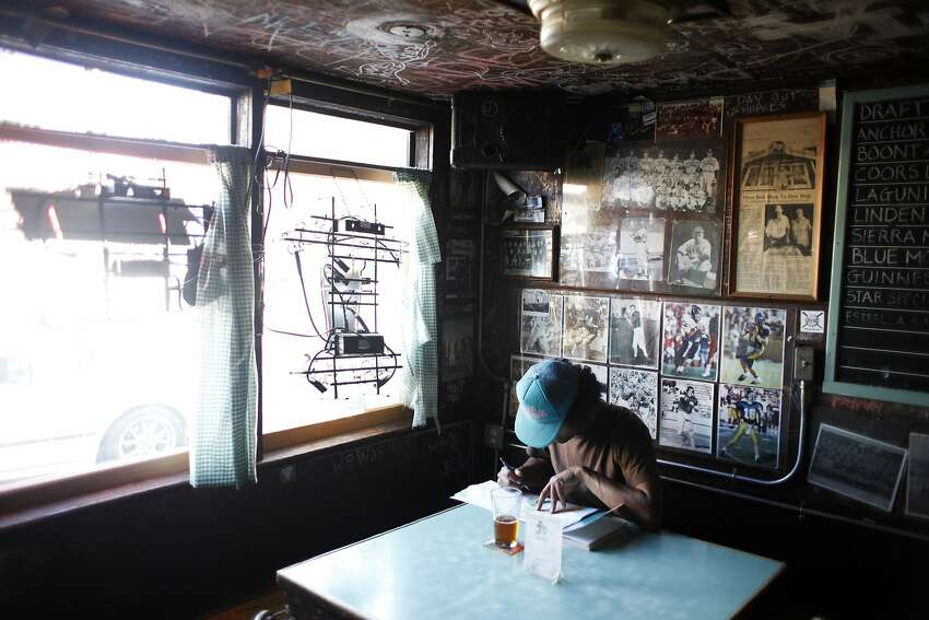 Daniel Lumbreras checks a map while planning a bike trip at the no-frills Kingfish Pub and Cafe in Oakland.