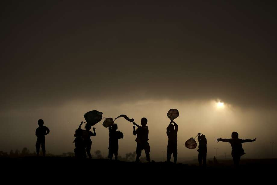 One man's trash is a child's toy: Afghan refugee children use discarded plastic bags as kites as the sun sets on the outskirts of Islamabad. Photo: Muhammed Muheisen, Associated Press