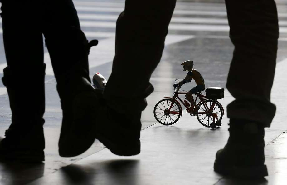 Tiny bicyclist or giant feet?The training wheels are a giveaway - it's a radio-controlled toy for sale in   a rail station shop in Milan, Italy. Photo: Luca Bruno, Associated Press